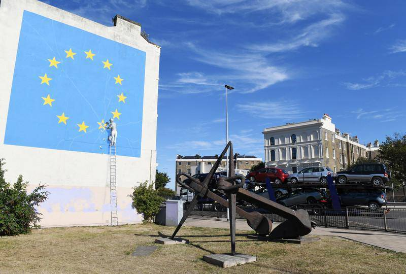 epa06920756 A view of a Brexit-inspired mural by anonymous British street artist Banksy depicting the European flag in Dover, Britain, 31 July 2018. The graffiti that appeared on a building near Dover's ferry terminal shows a worker removing one of the 12 stars from the EU flag.  EPA-EFE/FACUNDO ARRIZABALAGA