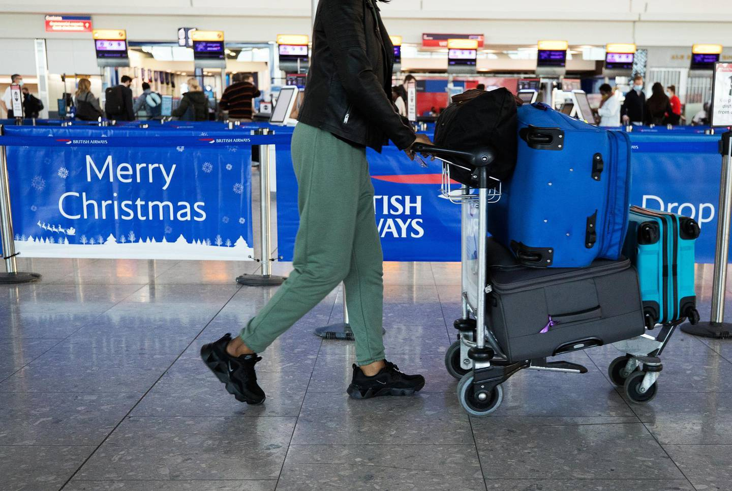 A passenger passes a 'Merry Christmas' sign in the check-in area in at London Heathrow Airport Ltd. in London, U.K., on Saturday, Dec. 19, 2020. The pandemic has put a third of all tourism jobs at risk, and airlines around the world have said they need as much as $200 billion in bailouts. Photographer: Chris Ratcliffe/Bloomberg