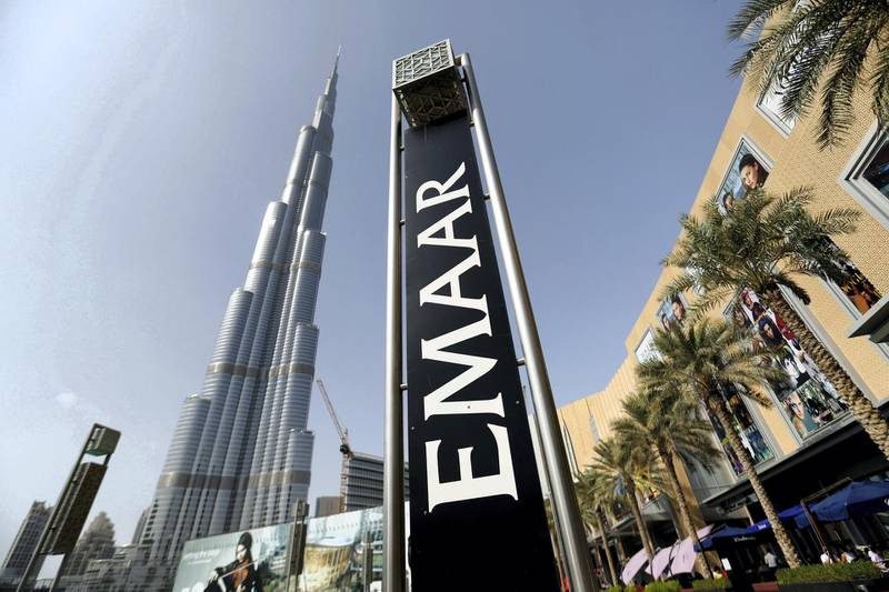 An Emaar Properties PJSC sign stands beside billboards promoting the Opera district developments near the Burj Khalifa tower in Dubai, United Arab Emirates, on Friday, Nov. 7, 2014. Dubai invested billions of dollars to become a regional trade, tourism and financial hub although it doesn't have a substantial oil revenue like fellow Gulf Arab sheikhdoms. Photographer: Chris Ratcliffe/Bloomberg
