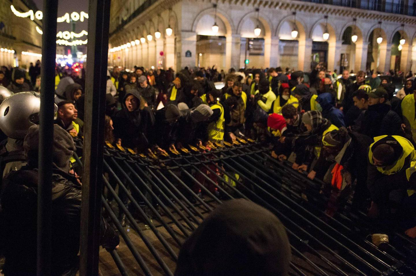 """TOPSHOT - Protestors wearing a yellow vest (Gilets jaunes) pull down the grating of the Tuileries Gardens next to the rue de Rivoli, in central Paris, during a demonstration against the rising oil prices and living costs, on December 1, 2018. Police and anti-government protesters clashed near the Champs-Elysees and in other parts of central Paris on December 1 with demonstrators hurling rocks and paint at riot police who responded with tear gas. The clashes came as thousands took part in a third weekend of """"yellow vest"""" protests which have morphed from anger over fuel taxes into a broader anti-government movement. / AFP / -"""