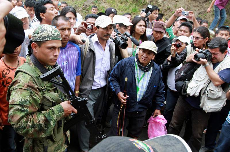 FILE PHOTO: A Revolutionary Armed Forces of Colombia (FARC) member watches a group of indigenous people as they walk past an illegal checkpoint at one of Toribio's main access road, in the province of Cauca, July 11, 2012. Colombian helicopter gunships strafed suspected rebel hideouts and guerrillas set up roadblocks as President Juan Manuel Santos visited the nation's volatile south on Wednesday amid growing criticism that security has deteriorated. REUTERS/Jaime Saldarriaga/File Photo