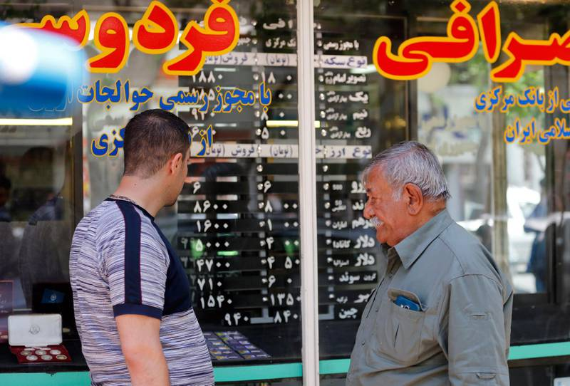 epa06660327 Iranians check the currency rate around an exchanges shop in Tehran, Iran, 10 April 2018. Media reported that President Hassan Rouhani and his cabinet have been criticized for the slide of the currency, as the US dollar is risen by 40 percent against the rial, which comes as US President Donald Trump threatens to pull out of a nuclear deal and re-impose potentially crippling sanctions. Iran moved to enforce a single exchange rate to the dollar, banning all unregulated trading after the country's currency, the rial felt in low against US dollar.  EPA/ABEDIN TAHERKENAREH