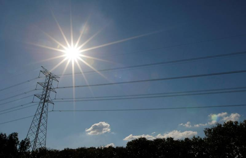 FILE PHOTO: The sun shines over a high tension power line in an industrial area of Sydney May 4, 2009. REUTERS/Tim Wimborne/File Photo