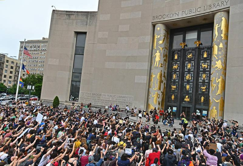 """Protesters take a knee and raise their fists during a """"Black Lives Matter"""" demonstration in front of the Brooklyn Library and Grand Army Plaza on June 5, 2020 in Brooklyn, New York, amid ongoing protests over the death in police custody of George Floyd. - The United States has seen more than a week of nationwide protests over the death in police custody of George Floyd, captured in a shocking video showing white officer Derek Chauvin kneeling on Floyd's neck for nearly nine minutes as he pleaded for his life. (Photo by Angela Weiss / AFP)"""