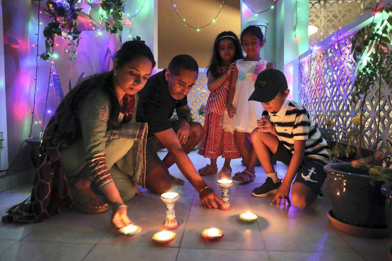 DUBAI, UNITED ARAB EMIRATES , November 14 – 2020 :- Baljeet Singh with his wife Rajwinder Kaur and kids light the lamps for Diwali festival at his home in Dubai. Diwali is the Indian festival of lights. People do prayers and exchange gifts and sweets on this day. (Pawan Singh / The National) For News/Standalone/Online/Instagram/Big Picture