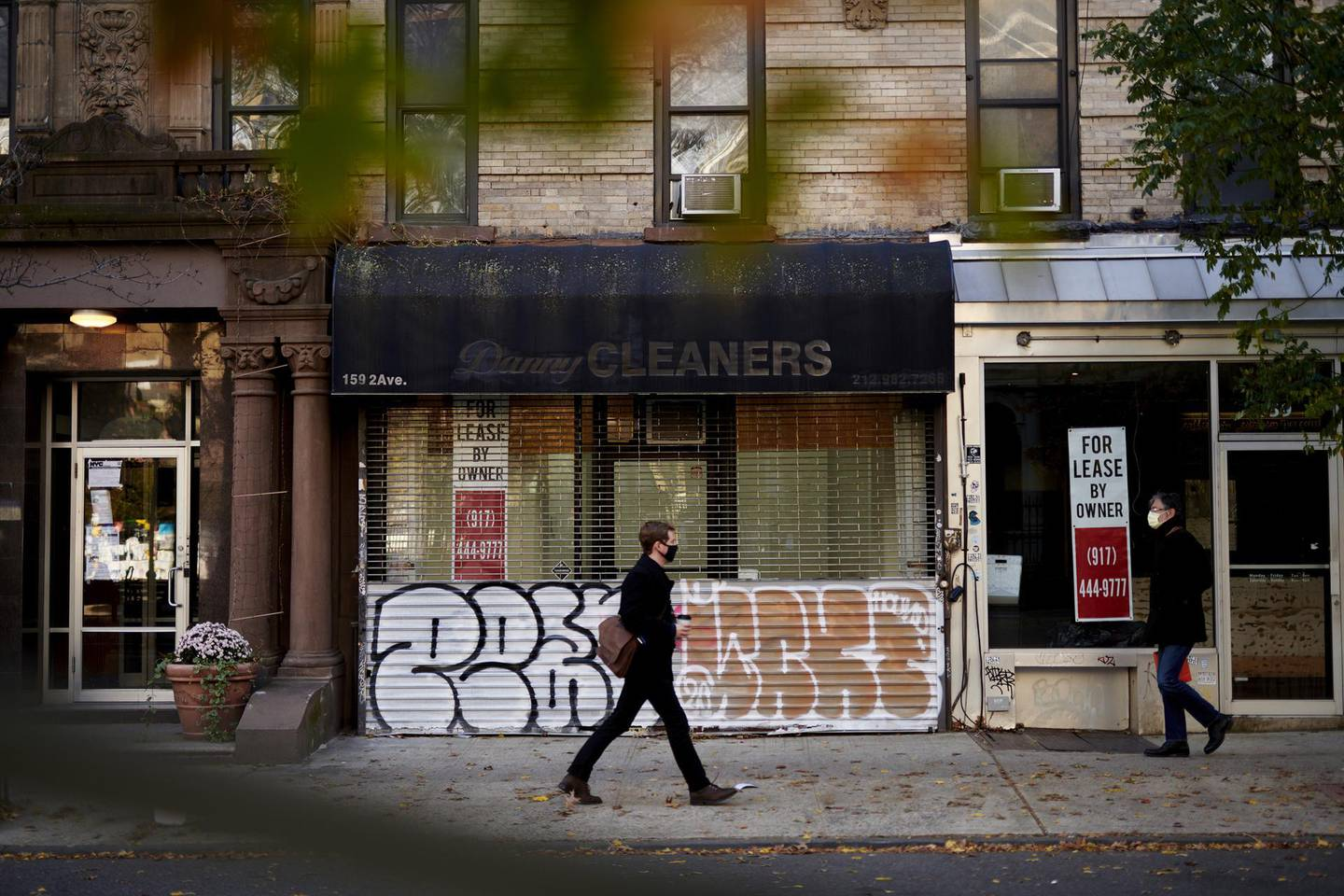 Pedestrians wearing protective masks pass in front of a permanently closed dry cleaners store and an empty storefront for lease in New York, U.S., on Thursday, Nov. 19, 2020. One in six dry cleaners have closed or gone bankrupt in the U.S. already, and many won't survive without more stimulus, according to the National Cleaners Association. Photographer: Gabby Jones/Bloomberg