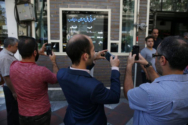 Iranians take pictures of an exchange shop screen showing various currency rates in downtown Tehran, Iran, Tuesday, Oct. 2, 2018. Iran's currency, the rial, unexpectedly rallied Tuesday after weeks of depreciation following President Donald Trump's decision to withdraw America from Tehran's nuclear deal with world powers, sending Iranians rushing to exchange shops to cash in. (AP Photo/Vahid Salemi)