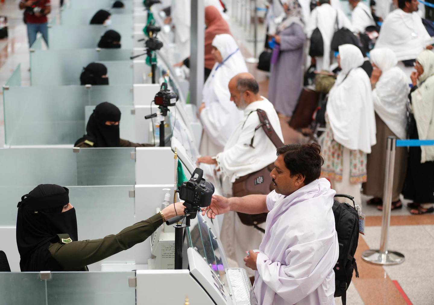 Saudi female officers from  the national security forces, register and check pilgrims at the Hajj Terminal at Jiddah airport, Saudi Arabia, Saturday, Aug. 3, 2019.  The annual Islamic pilgrimage draws millions of visitors each year, making it the largest yearly gathering of people in the world.  (AP Photo/Amr Nabil)