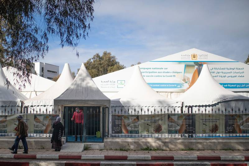 People walk past a bivouac where clinical trials for covid-19 vaccines are conducted, in Rabat, Morocco, Monday, Dec. 7, 2020. (AP Photo/Mosa'ab Elshamy)