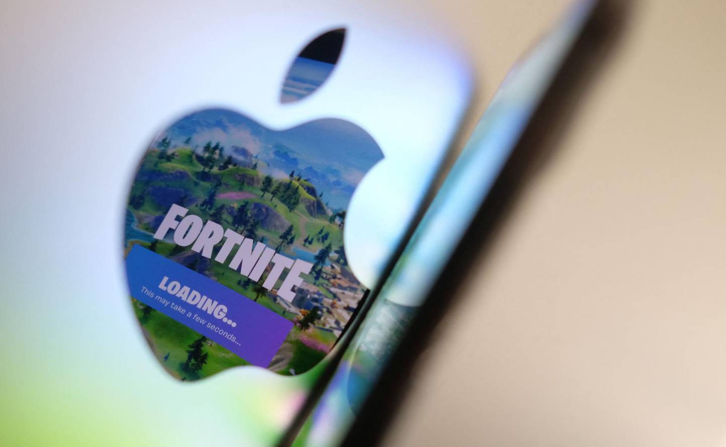 This illustration photo shows the opening screen of Epic Games' Fortnite reflecting onto the Apple logo of the back of an I-mac in Los Angeles on  May 3, 2021. In a court clash with potentially huge repercussions for the world of mobile tech, Fortnite maker Epic Games takes on Apple starting on May 3, 2021, aiming to break the grip of the iPhone maker on its online marketplace. -   / AFP / Chris DELMAS