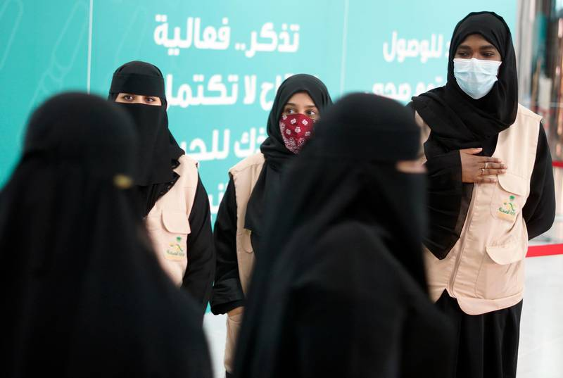 Health workers greet people after they receive their vaccine at a new coronavirus vaccination center, at the Jiddah old airport, Saudi Arabia, Thursday, Jan. 14, 2021. The Saudi Ministry of Health called on citizens and residents to take the vaccine for free. (AP Photo/Amr Nabil)
