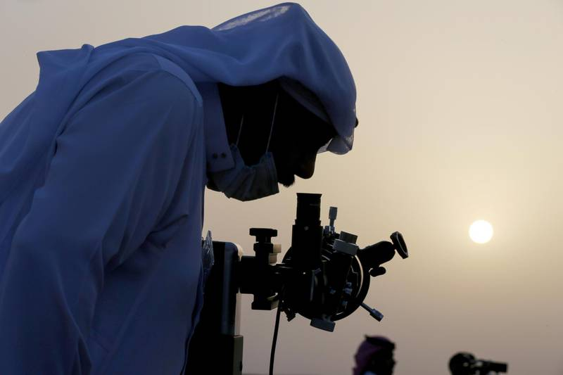 A member of the moon sighting committee looks through a telescope to view the moon ahead of Ramadan to mark the beginning of the holy fasting month, near Riyadh, Saudi Arabia, April 12, 2021. REUTERS/Ahmed Yosri     TPX IMAGES OF THE DAY