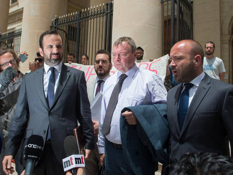 Claus-Peter Reisch, the German captain of Lifeline, a private ship that rescues migrants, is flanked by his lawyers as he leaves after an arraignment hearing in Valletta, Malta's capital, Monday, July 2, 2018. The Lifeline rescued 234 migrants in waters off Libya, then headed to Malta after Italy refused entrance to the ship. Reisch was charged with using the boat in Maltese waters without proper registration or license. (AP Photo/str)