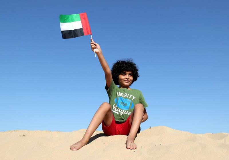 Dubai, United Arab Emirates - December 02, 2020: National Day. Hussein aged 8 waves his flag in the desert on National day. Wednesday, December 2nd, 2020 in Dubai. Chris Whiteoak / The National
