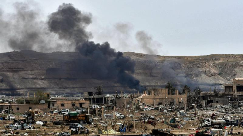 """This picture taken on March 24, 2019 shows smoke rising behind destroyed vehicles and damaged buildings in the village of Baghouz in Syria's eastern Deir Ezzor province near the Iraqi border, a day after the Islamic State (IS) group's """"caliphate"""" was declared defeated by the US-backed Kurdish-led Syrian Democratic Forces (SDF). (Photo by GIUSEPPE CACACE / AFP)"""