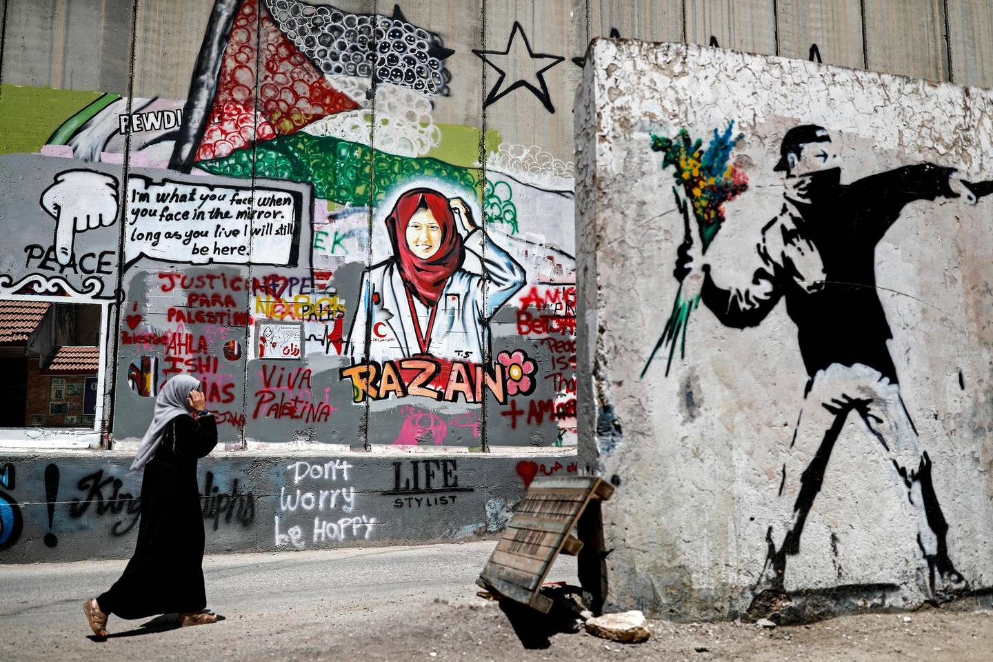 A Palestinian woman walks past fresh graffiti painted on Israel's controversial separation barrier in the occupied West Bank city of Bethlehem on June 22, 2018, by Palestinian street artist Taqi Sbateen depicting Razan Al Najjar (C), a paramedic nurse from Gaza who was killed by an Israeli sniper during a protest along the Israeli fence in Gaza. / AFP PHOTO / THOMAS COEX / RESTRICTED TO EDITORIAL USE - MANDATORY MENTION OF THE ARTIST UPON PUBLICATION - TO ILLUSTRATE THE EVENT AS SPECIFIED IN THE CAPTION