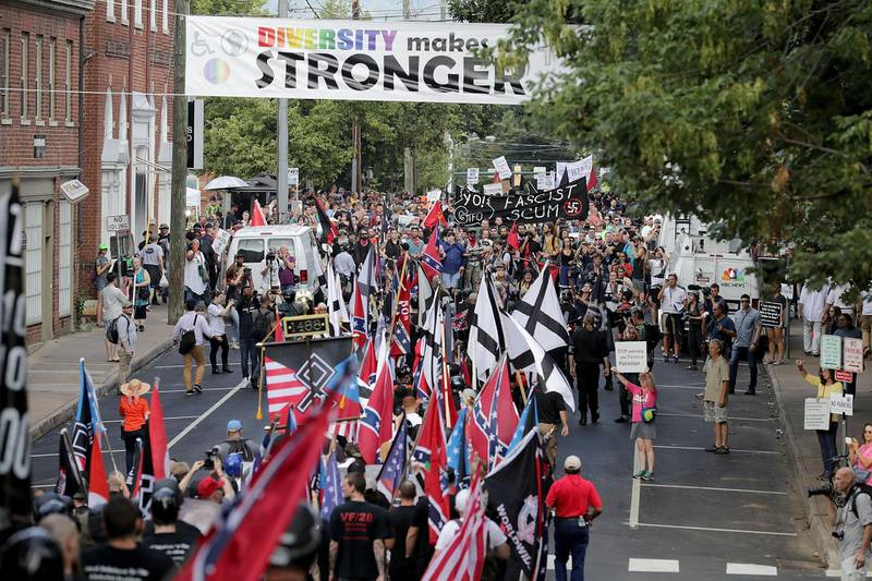 """CHARLOTTESVILLE, VA - AUGUST 12: Hundreds of white nationalists, neo-Nazis and members of the """"alt-right"""" march down East Market Street toward Emancipation Park during the """"Unite the Right"""" rally August 12, 2017 in Charlottesville, Virginia. After clashes with anti-fascist protesters and police the rally was declared an unlawful gathering and people were forced out of Emancipation Park, where a statue of Confederate General Robert E. Lee is slated to be removed.   Chip Somodevilla/Getty Images/AFP"""