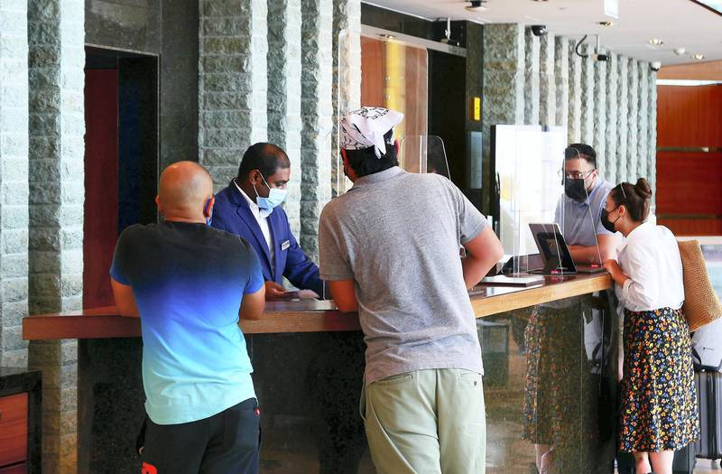 Staff checking the PCR negative test or Al Hosn app of the guests before check in at the Radisson Blu hotel in Dubai Internet City in Dubai on June 11,2021. Pawan Singh / The National. Story by Patrick
