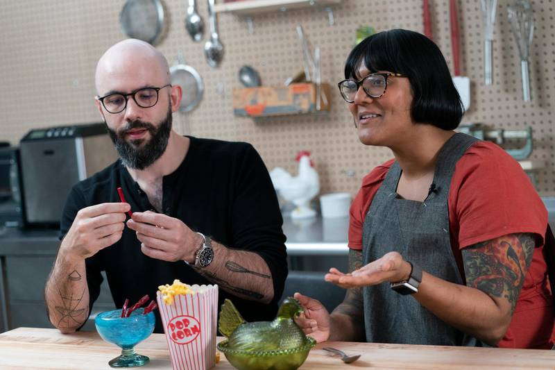 """In this Oct. 7, 2020 photo, Andrew Rea, founder of the Binging with Babish network, left, tastes a beet parsnip licorice created by chef Sohla El-Waylly, during a taping of the """"Stump Sohla"""" series in New York. (AP Photo/Mary Altaffer)"""