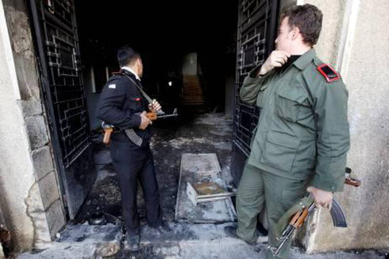 """Syrian policeman, left, and army soldier, right, look inside the burned court building that was set on fire by Syrian anti-government protesters, in the southern city of Daraa, Syria, Monday March 21, 2011. Mourners chanting """"No more fear!"""" have marched through a Syrian city where anti-government protesters had deadly confrontations with security forces in recent days. The violence in Daraa, a city of about 300,000 near the border with Jordan, was fast becoming a major challenge for President Bashar Assad, who tried to contain the situation by freeing detainees and promising to fire officials responsible for the violence. (AP Photo/Hussein Malla) *** Local Caption ***  XHM113_Mideast_Syria.jpg"""