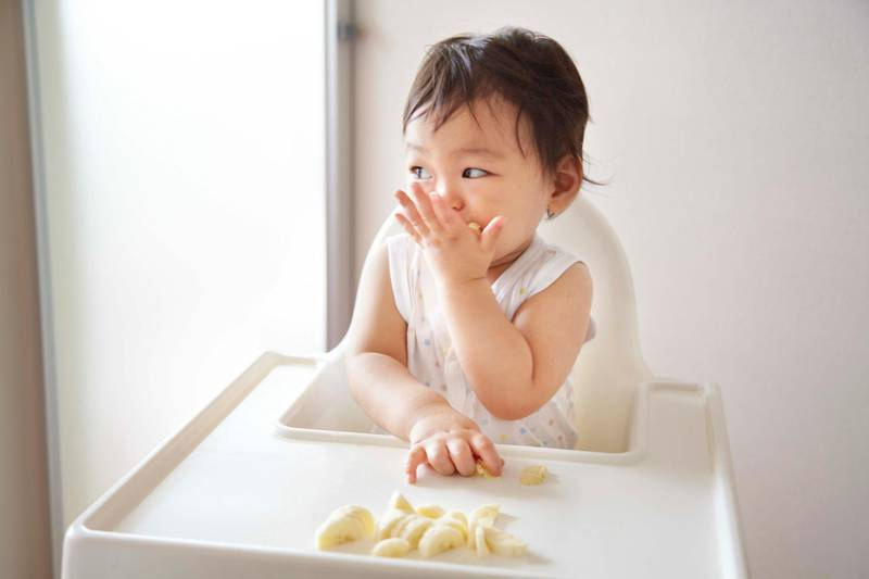 A baby boy eating banana in a high chair. Getty Images