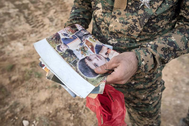 A Syrian Democratic Forces fighter searches the possessions of civilians who fled the last pocket of ISIS territory in Syria outside Baghouz, 28 February 2019. Campbell MacDiarmid