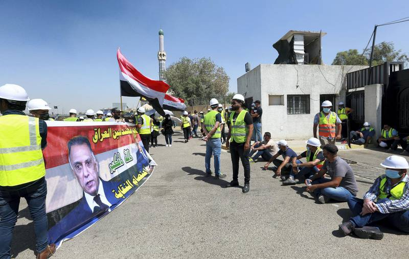 epa08673112 Jobless graduates carry the picture of Iraqi Prime Minister Mustafa Al-Kadhimi and the Iraqi national flag during a protest near the green zone in central Baghdad, Iraq, 16 September 2020. Thousands of university graduates and jobless continue their protests against the lack of job opportunities and basic services, near the heavily fortified Green Zone which houses the Iraqi government offices in Baghdad.  EPA-EFE/AHMED JALIL *** Local Caption *** 56346529