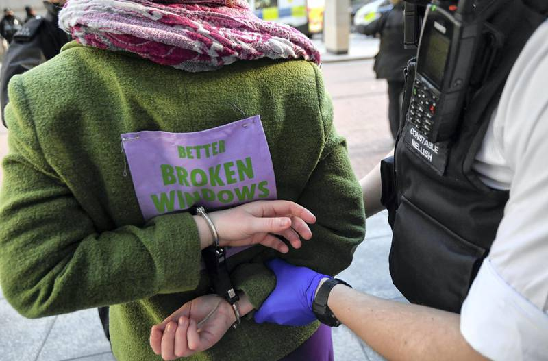 A police officer detains an activist from the Extinction Rebellion, a global environmental movement, outside the Barclays offices in Canary Wharf, London, Britain, April 7, 2021. REUTERS/Toby Melville
