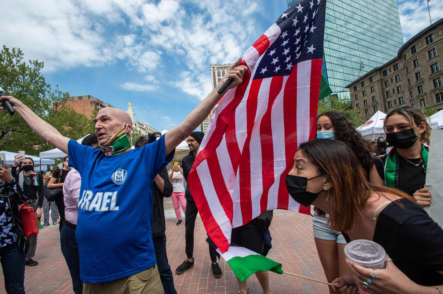 """A man, who claims to have been a member of the Israeli army for 32 years, is surrounded by pro-Palestinian supporters who shout at him and eventually steal his flag during a rally in support of Palestine in Copley Square in Boston, Massachusetts, May 15, 2021.  Speakers called for an end of international and US funding of Isreal's military. US President Joe Biden, in a phone call with Israeli Prime Minister Benjamin Netanyahu, expressed his """"grave concern"""" Saturday over the flareup of violence in Israel and Gaza, the White House announced.  / AFP / Joseph Prezioso"""