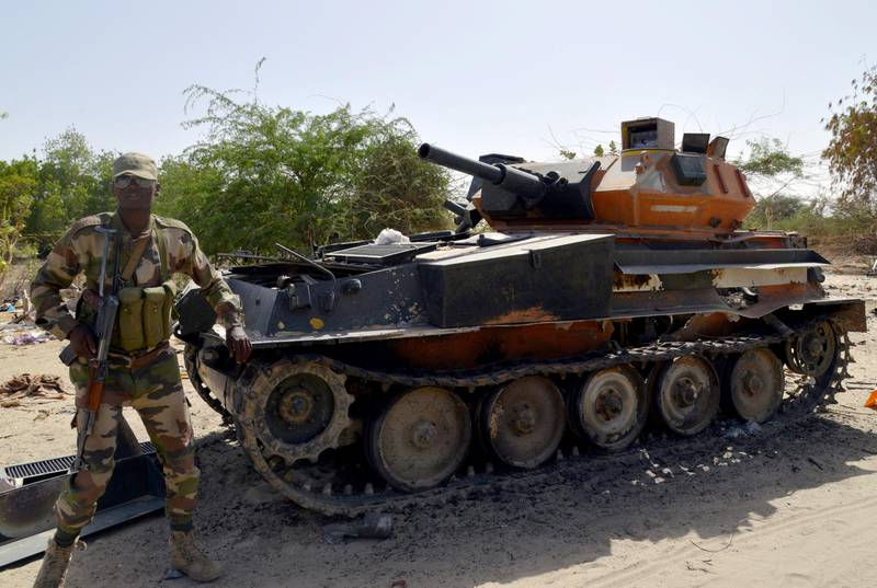 A soldier from the Niger army stands next to a burnt out  tank belonging to the Boko Haram militants, on May 25, 2015 in Malam Fatori, in northern Nigeria, near the border with Niger, where the Niger and Chadian army troops, are working together in support of Nigerian forces, to fight the Boko Harm Islamists. Boko Haram, which wants to create a hardline Islamic state in northeast Nigeria, has been pushed out of captured towns including Malam Fatori, and territory, since February by Nigerian troops with assistance from Niger, Chad and Cameroon. AFP PHOTO / ISSOUF SANOGO (Photo by ISSOUF SANOGO / AFP)