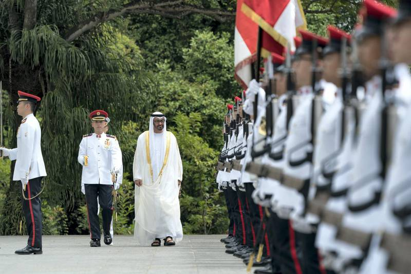 SINGAPORE, SINGAPORE - February 28, 2019: HH Sheikh Mohamed bin Zayed Al Nahyan, Crown Prince of Abu Dhabi and Deputy Supreme Commander of the UAE Armed Forces (C) inspects honor guard during a reception hosted by HE Halimah Yacob, President of Singapore (not shown), at the Istana presidential palace.  ( Eissa Al Hammadi for the Ministry of Presidential Affairs ) ---