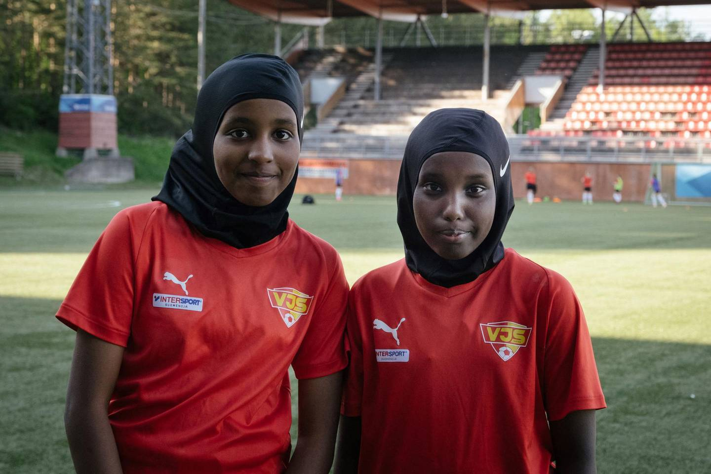 """Kamila Nuh (L) and Nasro Bahnaan Hulbade, both 13 years old, pose for photos at the beginning of a football training session at the MUP Stadium in Vantaa, Finland, on June 1, 2021.   Finland's football association has begun offering a free """"sports hijab"""" to any player who wants one, in a move designed to attract a greater diversity of players into the sport. So far, the FA has distributed """"dozens"""" of the headscarves, which are made out of technical, stretchy fabric, Heidi Pihlaja, head of development of women and girls' football, told AFP.   / AFP / Alessandro RAMPAZZO"""