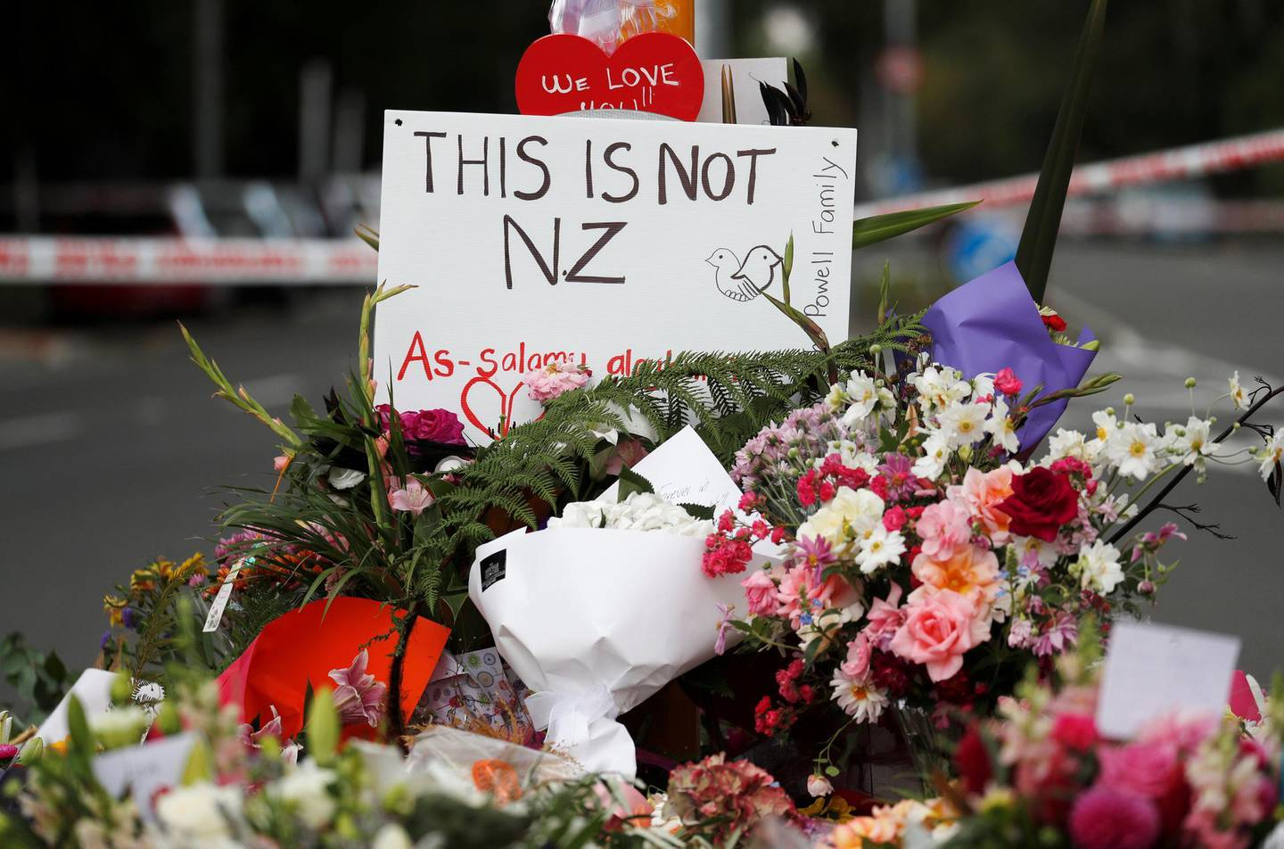 Flowers and signs are seen at a memorial as a tribute to victims of the mosque attacks, near Linwood mosque in Christchurch, New Zealand, March 16, 2019. REUTERS/Edgar Su