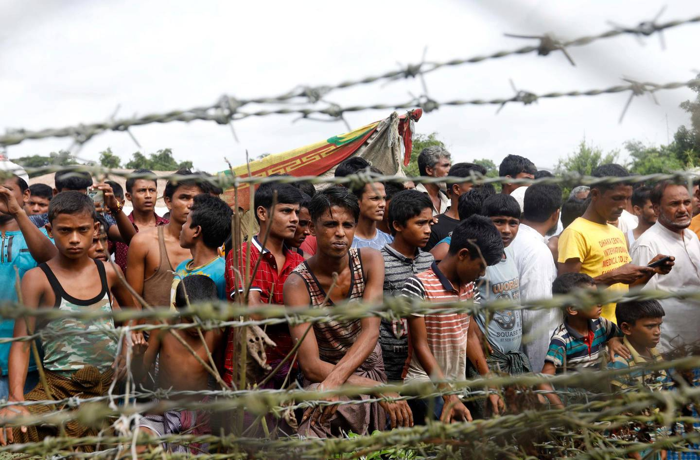 epa07031825 (FILE) - Rohingya refugees gather near a fence at the 'no man's land' zone at the Bangladesh-Myanmar border in Maungdaw district, Rakhine State, western Myanmar, 24 August 2018 (reissued 19 September 2018). Chief Prosecutor of the International Criminal Court (ICC), Fatou Bensouda released a statement on 18 September 2018, announcing the opening of a preliminary examination into Myanmar's alleged deportation of Rohingya people from Myanmar to Bangladesh, as well as other potential crimes. The preliminary examination will determine whether there is enough evidence to proceed with a full investigation. Since Myanmar is not an ICC state party, but Bangladesh is, the court 'may exercise jurisdiction over conduct to the extent it partly occurred on the territory of Bangladesh,' she said. A UN independent mission on Myanmar released a report on 18 September 2018, examining the situation in three Myanmar states over 15 months, making recommendations to the UN, the international community and to the Myanmar Government to investigate and prosecute the country's military leaders for 'genocide, crimes against humanity and war crimes.' Thousands of Rohingya people fled the violence in Myanmar since August 2017, to find refuge in neighboring Bangladesh.  EPA/NYEIN CHAN NAING *** Local Caption *** 54573514