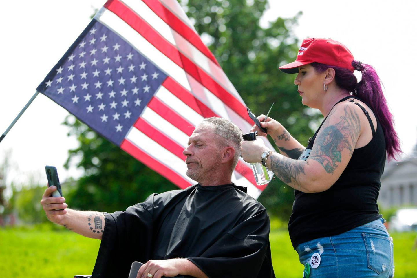 Trump supporter Laina Moore of Elma, Washington gives a haircut to Darren Culbertson of Yelm, Washington on the lawn of the State Capitol as people protest Governor Jay Inslee's stay-at-home order which prohibits barbers and stylists from taking clients, in Olympia, Washington on May 9, 2020. The Washington State Patrol estimates about 1,500 people rallied against Governor Jay Inslee's stay-at-home order. / AFP / Jason Redmond