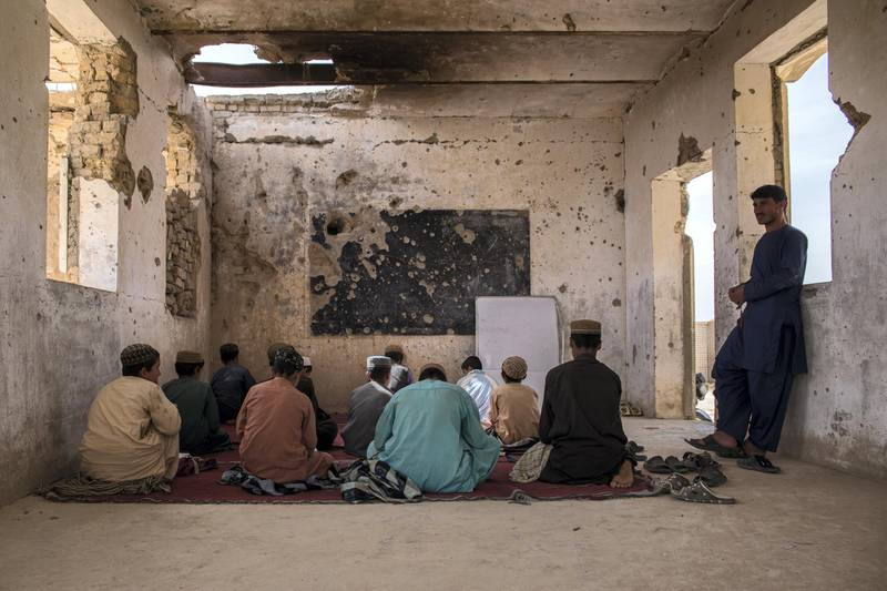 Students sit in their classroom at Assad Suri Primary School in Kandahar's Zhari District. Many of the buildings have been destroyed in airstrikes and by blasts, leaving classrooms exposed and bullet riddled. Part of the school continues to be occupied by the local police.