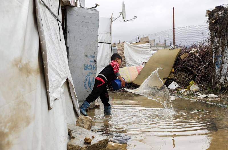 TOPSHOT - A Syrian child uses a bucket to bale out water from his tent at a refugee camp on the outskirts of the town of Zahle in Lebanon's Bekaa Valley on January 26, 2018. Lebanon, a country of four million, hosts just under a million Syrians who have sought refuge from the war raging in their neighbouring homeland since 2011, many of whom live in informal tented settlements in the country's east and struggle to stay warm in the winter. / AFP PHOTO / JOSEPH EID