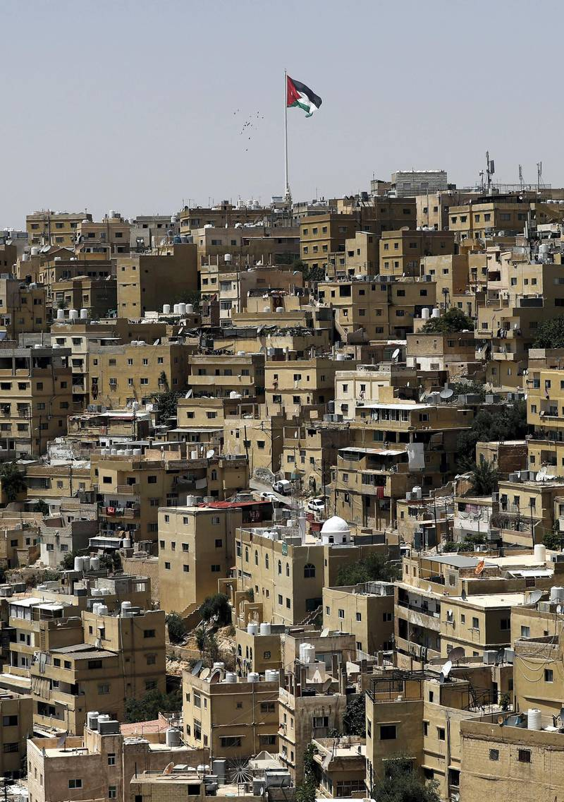 A general view taken from Jabal al-Qala district shows a Jordanian flag fluttering above the Jordanian capital Amman on June 8, 2018.  Jordan's authorities may have shelved a proposed income tax hike after a week of protests -- but they still face the tricky task of balancing popular demands with the need to fix the economy. The controversial legislation sparked some of the biggest economic demonstrations to hit the country in the past five years, forcing a change of prime minister, with Hani Mulki stepping down in favour of Harvard-trained economist Omar al-Razzaz.   / AFP PHOTO / AHMAD GHARABLI