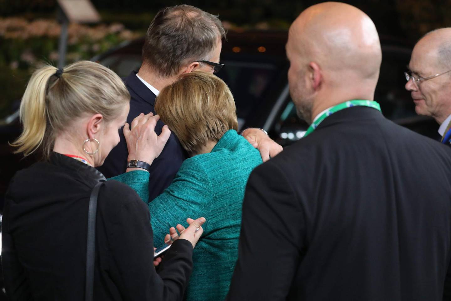 German chancellor Angela Merkel rests on the shoulder of Finland prime minister Juha Sipila before leaving after the first day of the European Council on june 29, 2018, in Brussel. European Union leaders reached a crucial deal on steps to tackle migration during all-night talks on June 29 after resolving a bitter row with Italy's hardline new premier. / AFP / Ludovic MARIN