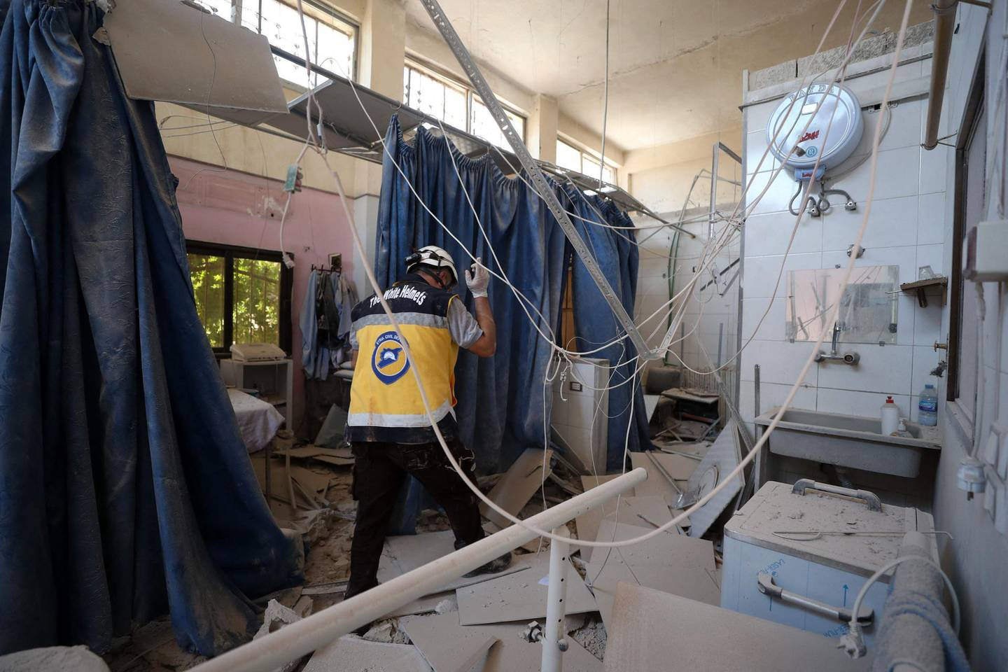 A member of Syria's Civil Defence service (White Helmets) inspects the damage on June 13, 2021, in one of the rooms of the Al-Shifaa hospital, a day after it was hit by artillery shells in the rebel-held northern Syrian city of Afrin, reportedly fired by pro-regime forces, killing at least 18 people, and wounding more than 23, according to a war monitor. The Syrian Observatory for Human Rights said a doctor, three hospital staff, two women and two children as well as a rebel commander were among the dead.  / AFP / OMAR HAJ KADOUR