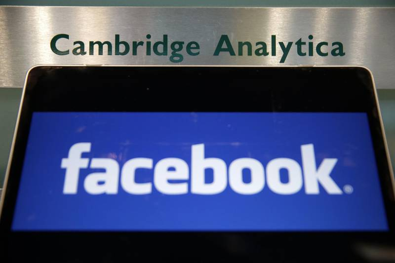 """(FILES) In this file photo taken on March 21, 2018 A laptop showing the Facebook logo is held alongside a Cambridge Analytica sign at the entrance to the building housing the offices of Cambridge Analytica, in central London. Cambridge Analytica, the UK marketing analytics firm at the heart of the Facebook data scandal, announced on May 2, 2018, it was """"immediately ceasing all operations"""" and filing for insolvency in Britain and the United States. """"It has been determined that it is no longer viable to continue operating the business,"""" the company, accused of misusing tens of millions of Facebook users' data, said in a statement. / AFP PHOTO / Daniel LEAL-OLIVAS"""