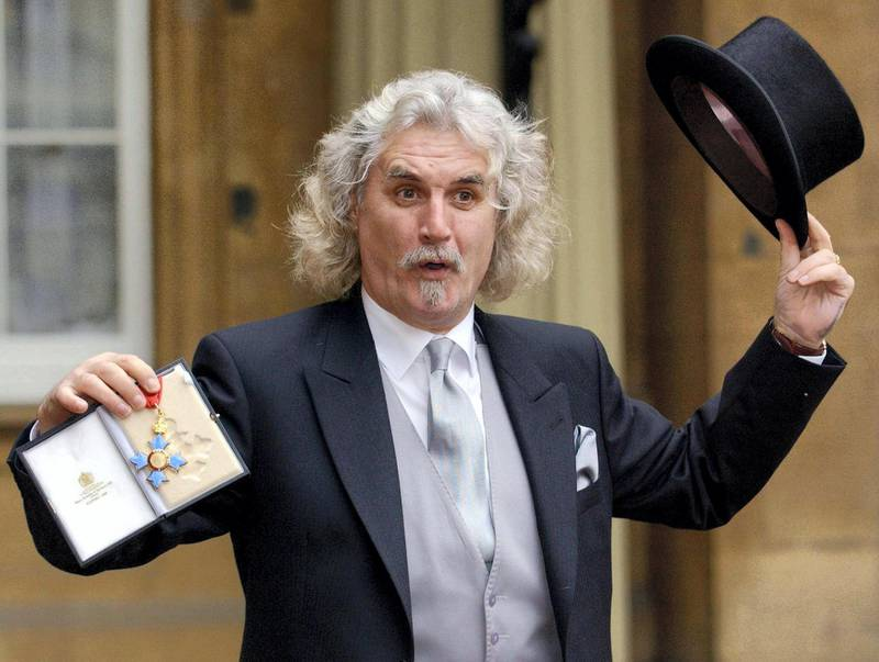 Scottish comedian and actor Billy Connolly shows off his CBE he received 03 December, 2003 from the Prince of Wales at Buckingham Palace, London.     AFP PHOTO/FIONA HANSON/WPA POOL (Photo by FIONA HANSON / POOL / AFP)