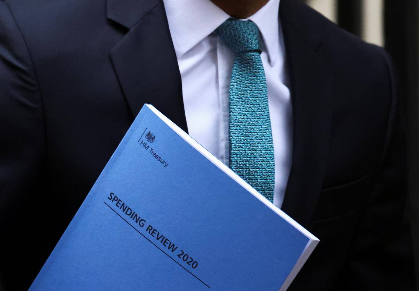 """Britain's Chancellor of the Exchequer Rishi Sunak carries the """"Spending Review 2020"""" document as he leaves Downing Street, in London, Britain, November 25, 2020. REUTERS/Henry Nicholls"""