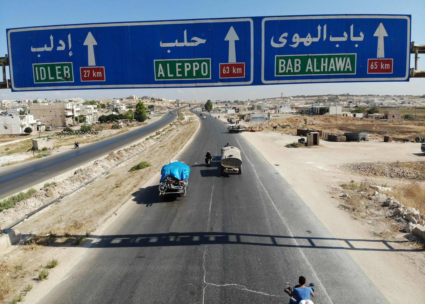 Syrian civilians flee on August 21, 2019 a conflict zone in Syria's rebel-held northwestern region of Idlib, where government bombardment has killed hundreds since late April. Damascus said on August 22 it is opening a corridor for civilians to leave the Idlib province. Damascus has opened such corridors out of other rebel bastions in the past as a prelude to retaking them either by force or through negotiated surrenders. The Idlib region, which sits on the Turkish border, is now the last major stronghold of opposition to the Russia-backed government of President Bashar al-Assad.  / AFP / Omar HAJ KADOUR