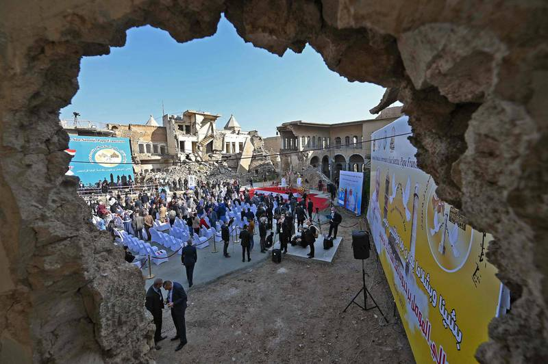 """Iraqis gather in the ruins of the Syriac Catholic Church of the Immaculate Conception (al-Tahira-l-Kubra), in the northern city of Mosul, amidst preparations ahead of the Pope's visit, on March 7, 2021.  Pope Francis, on his historic Iraq tour, visits today Christian communities that endured the brutality of the Islamic State group until the jihadists' """"caliphate"""" was defeated three years ago / AFP / Vincenzo PINTO"""