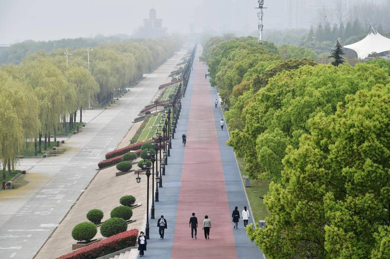 People wearing face masks walk at a riverside park in Wuhan of Hubei province, the epicentre of China's coronavirus disease (COVID-19) outbreak, March 26, 2020. REUTERS/Stringer  CHINA OUT.