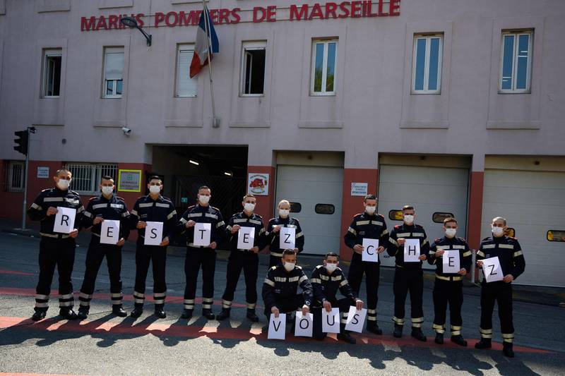 """TOPSHOT - French firefighters from Marin unit of Marseille wearing protective masks hold placards reading """" Stay at home """"  at the Saint Lazare barracks in Marseille on 03 April, 2020, during the strict lockdown in France to stop the spread of the novel coronavirus.  / AFP / Christophe SIMON"""