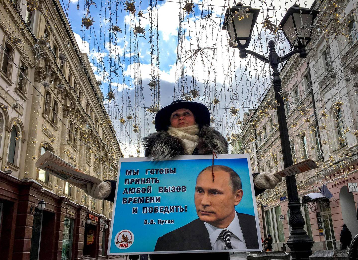 TOPSHOT - An activist distributes election leaflets in support of presidential candidate, President Vladimir Putin on a street in downtown Moscow on March 16, 2018. Russia will vote for president on March 18, 2018. / AFP PHOTO / Yuri KADOBNOV