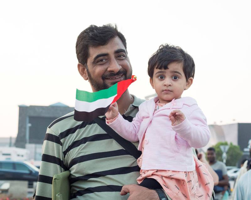 Abu Dhabi, United Arab Emirates - A father and daughter celebrating the UAE National day at Abu Dhabi Corniche, Breakwater.  Leslie Pableo for The National
