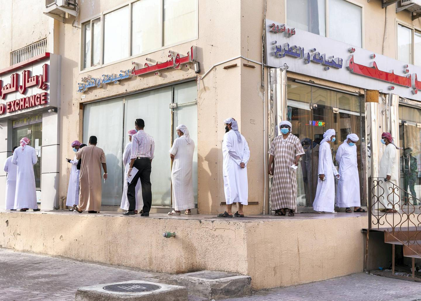 ABU DHABI, UNITED ARAB EMIRATES. 2- MAY 2020.Men line up at the money exchange in Baniyas neighborhood, as they prepare for Eid Al Fitr.(Photo: Reem Mohammed/The National)Reporter:Section: